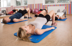 People doing exercise on gym floor mats